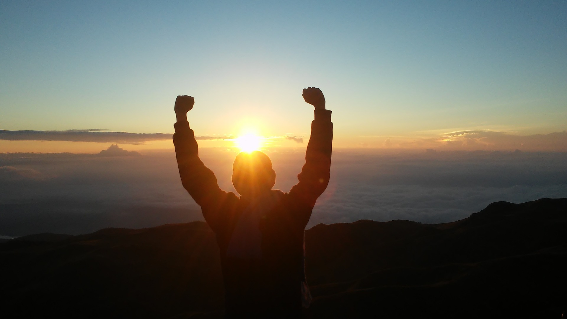 Man raising arms for victory looking over large landscape